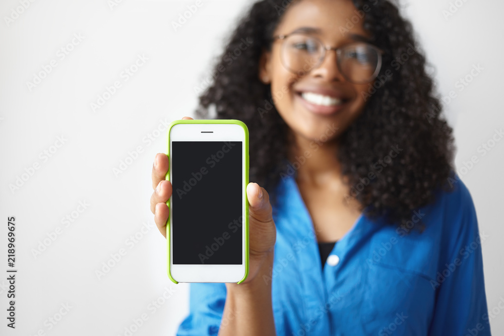 Fototapeta Picture of positive smiling young African American female in glasses holding generic mobile phone, showing blank display with copy space for your text or advertising content. Selective focus