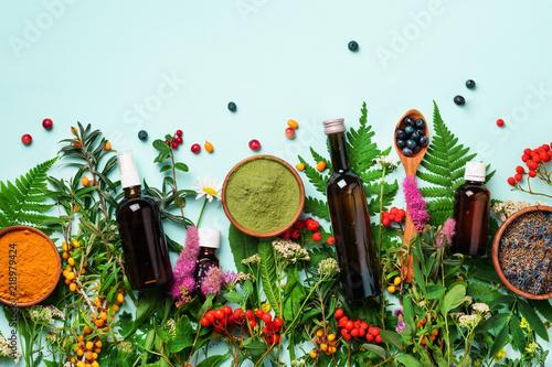 Obraz na płótnie Healthy super food, berries, turmeric, spirulina, omega acid capsules, vitamin c supplement, medicinal herbs and spices on blue background