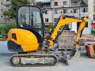 Yellow mini excavator on tracks for small construction works in hard-to-reach places or on narrow city streets, side view, summer day