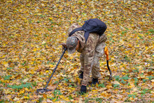 Man With A Metal Detecting Device Searches In The Autumn