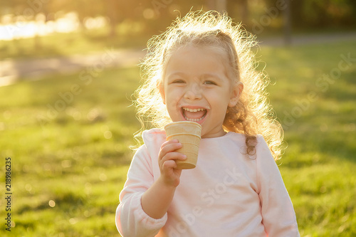 Fototapeta happy and little girl eating ice cream in summer park obraz na płótnie