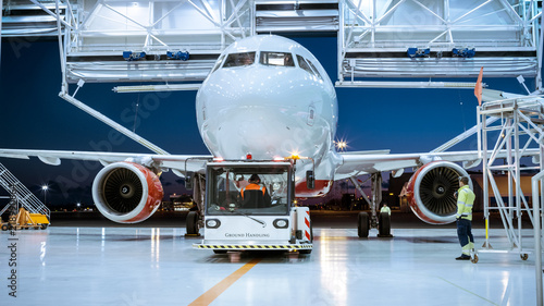 Fotografie, Obraz  Aircraft Maintenance Hangar Where New Airplane is Toed by a Pushback Tractor/ Tug onto Landing Strip