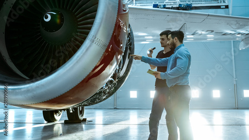 Fotografie, Obraz  In a Hangar Aircraft Maintenance Engineer Shows Technical Data on Tablet Computer to Airplane Technician, They Diagnose Jet Engine Through Open Hatch