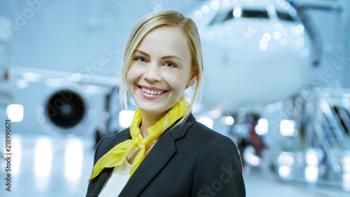 In a Aircraft Maintenance Hangar Young Beautiful Blonde Stewardess/ Flight Attendant Smiles Charmingly on Camera Canvas Print