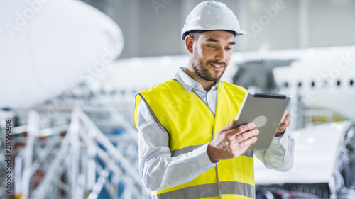 Leinwand Poster Portrait of Aircraft Maintenance Mechanic in Safety Vest using Tablet Computer