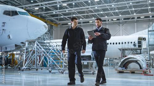 Fotografia Team of Aircraft Maintenance Mechanics Moving through Hangar