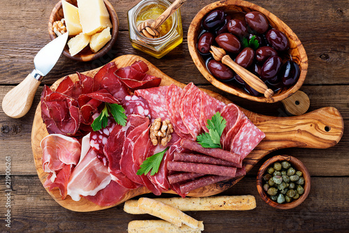 Obraz na płótnie Antipasto platter cold meat with breadsticks, prosciutto, slices ham, beef jerky, salami and cheese platter on wooden board over rustic background