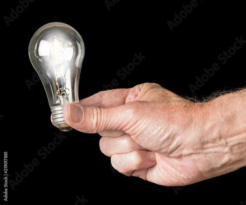 Obraz Mans hand holding an illuminated halogen lightbulb - fototapety do salonu