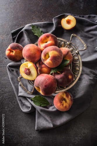 A group a ripe peaches in rustic bowl