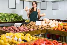 Smiling Female Seller Holding Yellow Gourd