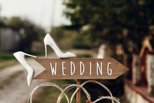 Beautiful White Shoes On Wooden Arrow With Wedding Text Sign. Rustic Wedding Concept. Pointing For Wedding Ceremony Location. Creative Ideas