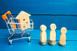 wooden house, supermarket trolley, people. real estate. Buying, selling and renting a house. Loan for an apartment, mortgage rate. Affordable housing for young families. auction, public sale