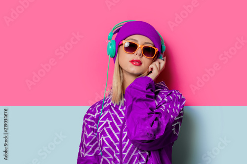 Tela  Young blonde girl in 90s sports jacket and hat on pink and blue background