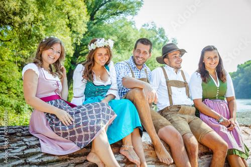 Valokuva  Oktoberfest Freunde in Lederhosen und Dirndl trinken Bier an der Isar