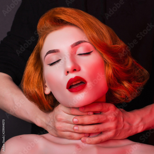 Men's hands stifle redhead girl on black background Tablou Canvas