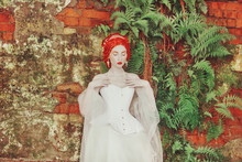 Fairytale Hero. Renaissance Redhead Princess With Hairstyle In Castle. Fabulous Rococo Duchess In White Dress Against The Backdrop Of Old Fern Wall. Duchess In Corset. Fairytale Princess In Palace