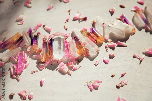 Colorful quartz crystals with pink rose leaves on wooden structure, flat lay background