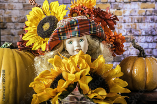 Photo child's doll with long blonde hair blue glass eyes and red hat surrounded by ora