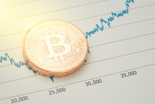 Bitcoin Cryptocurrency, Digital Money Price Turnaround Market Concept, Stack Of Physical Coins With B Sign Alphabet At The Lowest Point Befor Rising Price Graph Report With Golden Flare Light