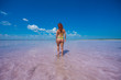 Girl standing on the ankle in a salt pink lake in the Altai. the girl in a candid yellow bikini stands back with her bare buttocks. Miracle of nature rose lake