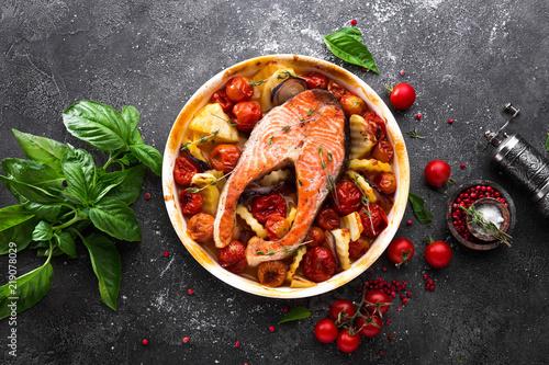 Grilled salmon fish steak with potato, onion and tomatoes. Baked salmon fish steak with vegetables