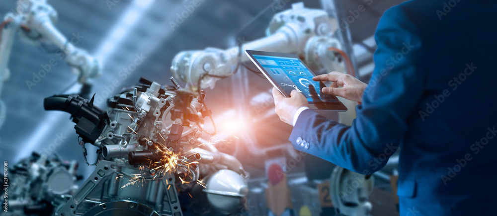 Fototapety, obrazy: Engineer manager checking and controling automation robot arms machine in intelligent factory industrial on real time monitoring system software. Welding robotics and digital manufacturing operation.