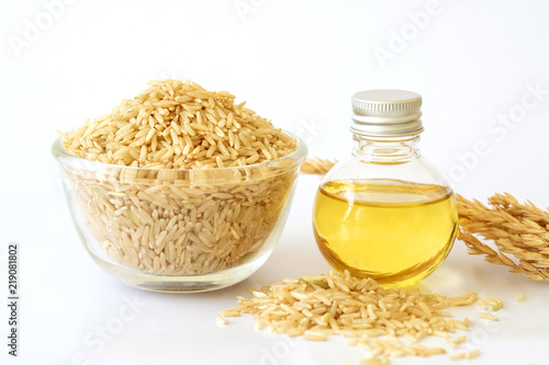 Close up brown rice seed and rice bran oil in bottle  and unmilled rice on a white background , good fats for healthy food