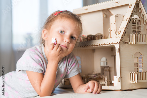 a girl playing with a dollhouse Canvas-taulu