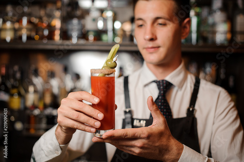 Poster de jardin Bar Attractive bartender holding a bloody mary cocktail with two olives and celery
