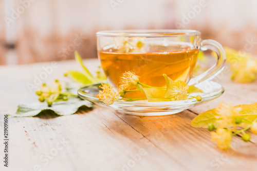 Cup of tea and linden on wooden background