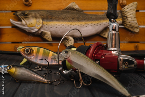Foto op Canvas Jacht Fishing tackle - fishing spinning, hooks and lures on darken wooden background. Top view.
