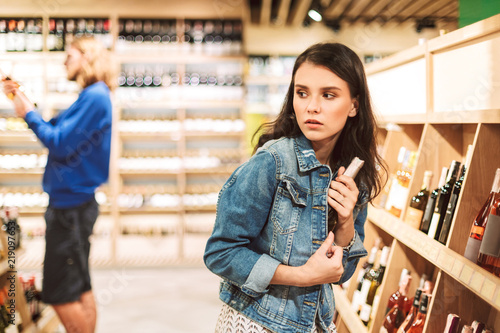 Fotomural  Young frightened woman in denim jacket trying steal bottle of wine in modern sup