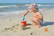 Cute little boy is building sand castle on the seashore