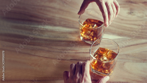 Canvas-taulu Hands of whisky bourbon in two glass on a grunge wooden background