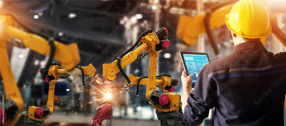 Fototapeta Engineer check and control welding robotics automatic arms machine in intelligent factory automotive industrial with monitoring system software. Digital manufacturing operation. Industry 4.0