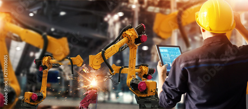 Photo Engineer check and control welding robotics automatic arms machine in intelligent factory automotive industrial with monitoring system software
