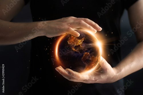 Fotografía  Hands holding global showing the world' s energy consumption at night, environment and energy conservation concept