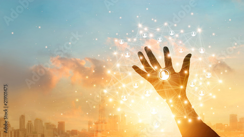 Businessman touching icon customer in hand with global network connection and data exchanges worldwide on city sunset background. Networking and technology concept