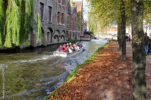 tourist boat going down canal in bruges belgium in autumn