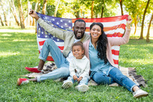 Smiling African American Parents And Daughter Holding American Flag At Picnic In Park