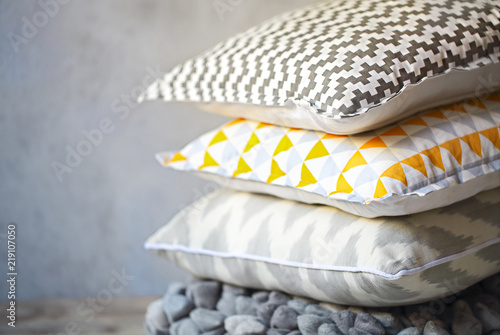 Fotografia  Yellow and grey pillows on the wall background
