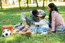 African American Soldier In Military Uniform Spending Time With Family At Picnic In Park