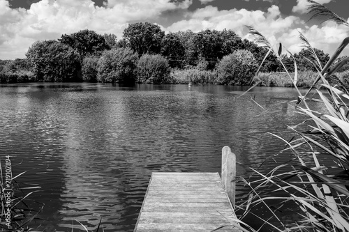 wooden jetty, jutting out into a calm swimming lake with trees in background