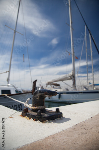 Fotografía  Some boats moored to black bollards in a marina on an island in the Mediterranea