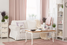 Real Photo Of Bright Provencal Sitting Room Interior With White Sofa, Wooden Coffee Table On Dirty Pink Carpet, Rack With Decor And Fresh Lavender