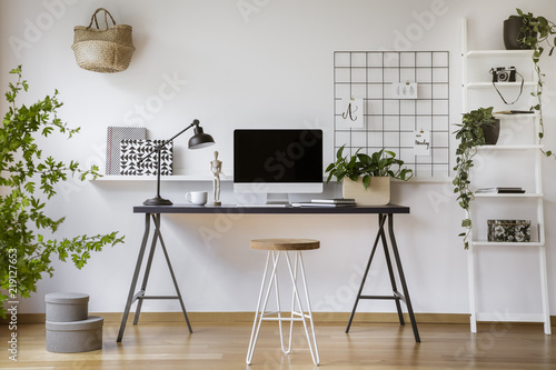 Fototapeta Hairpin stool standing by the wooden desk with mockup computer screen, metal lamp and coffee cup in real photo of white home office interior obraz
