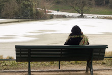 Woman Looking At A Frozen Lake