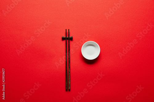 Photo  top view of arranged chopsticks and empty bowl on red backdrop