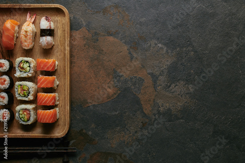 top view of arranged sushi set on wooden plate and chopsticks on dark surface Canvas Print