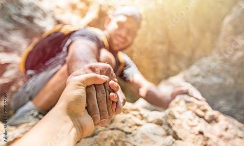 Fototapeta Adventurers helping each other to climb obraz
